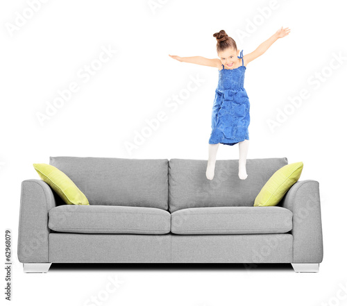 Happy female kid jumping on couch