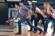 Friends cheering their friend while throwing bowling ball