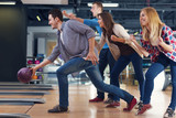 Fototapety Friends cheering their friend while throwing bowling ball