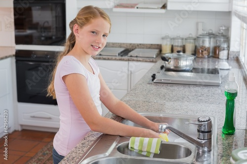 Portrait of a young girl standing near kitchen