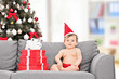 Little baby with Santa hat sitting on couch