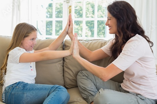 Mother and daughter with hands together on sofa