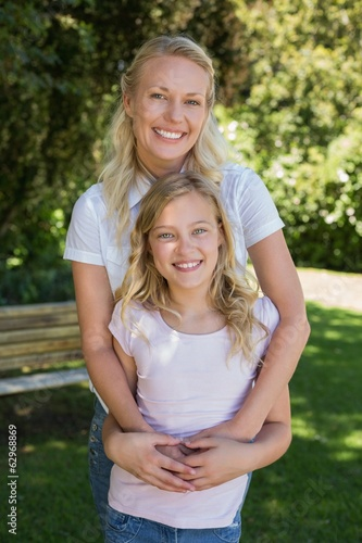 Happy woman embracing girl in park