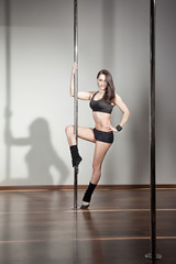 Attractive  young woman in a pole fitness class