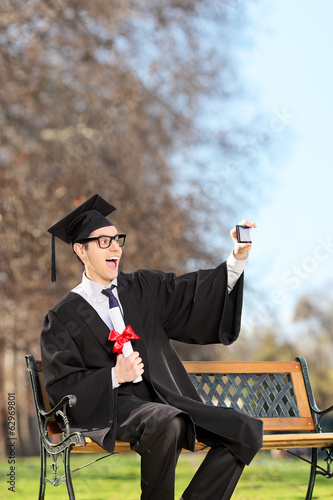 Man in graduation gown taking a selfie