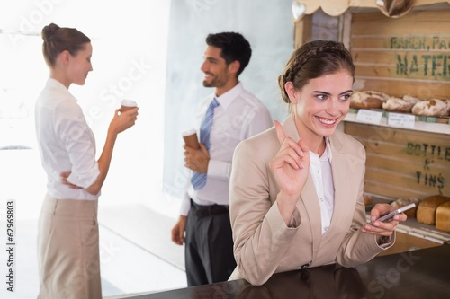 Businesswoman using mobile phone in office cafeteria