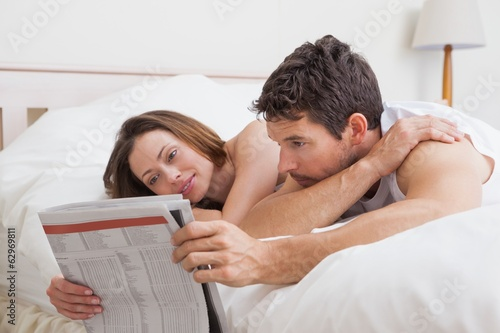 Couple reading newspaper together in bed