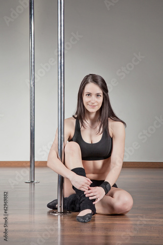 Attractive young woman  sitting on the floor in a pole fitness c