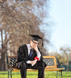 canvas print picture - Sad graduate student sitting on a bench in park