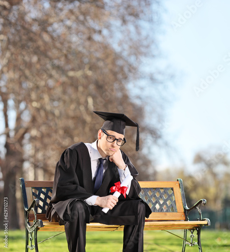 Sad graduate student sitting on a bench in park