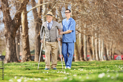 Senior and a male nurse walking in park