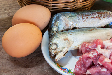 Fish, pork, eggs on a wooden floor.