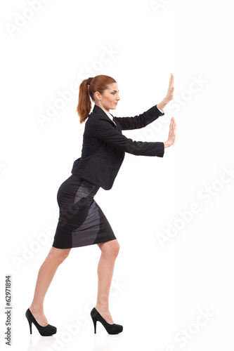 Businesswoman pushing the wall