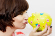 Young funny woman with decorative ceramic piggy bank