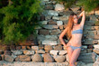 Woman in a swimwear at the stone wall