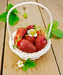 Strawberries in basket with flowers on board
