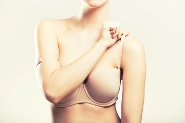 Woman holding bra strap, natural beauty