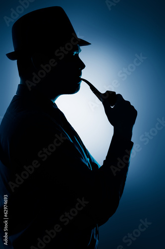 Silhouette of Man Smoking Pipe on a Spotlight Background