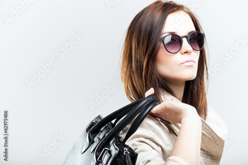 Elegant woman in coat with black leather bag