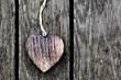 A wooden vintage heart on grunge wood planks. Symbol of love,