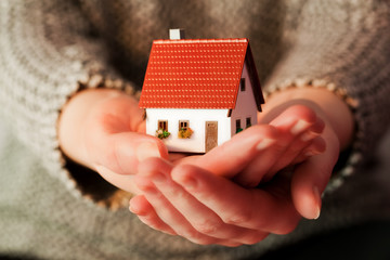 Woman holding a small new house in her hands. Real estate