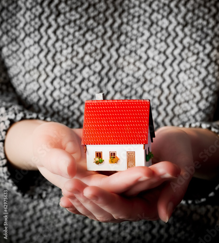 Woman holding a small new house in her hands. Mortgage