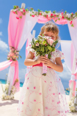 young happy kid girl in beautiful dress on tropical wedding setu