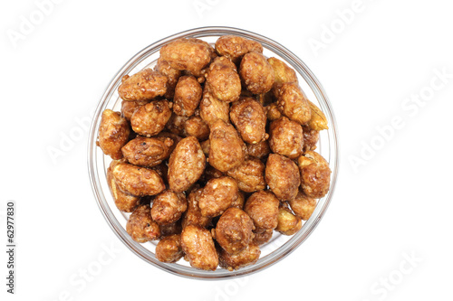 Roasted peanuts and sugar in a glass on a white background
