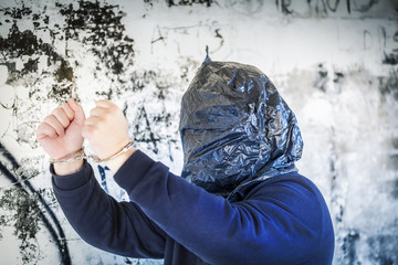 Hostage in handcuffs and with a bag on head near wall