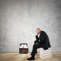 Thoughtful Businessman sitting on a stack of books