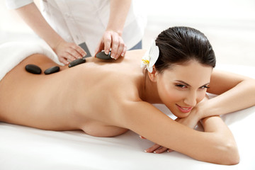 Spa Tretment. Beautiful Woman Getting Spa Hot Stones Massage © puhhha