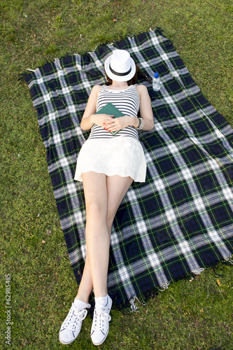 woman sleeping with a hat over her face in a park on grass