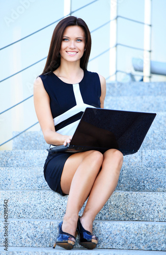 smiling young business woman using laptop on steps