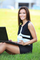 A happy business woman working on her laptop outside in the park