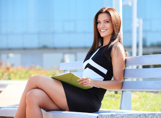 attractive young professional woman sitting in a park, smiling.
