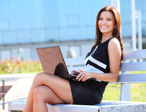 Young business woman sitting on a park bench and using laptop