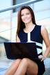 smiling young business woman using laptop on steps outdoors