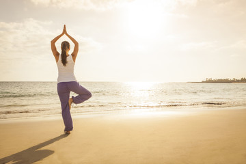 Young woman practicing tree yoga pose near the ocean during suns