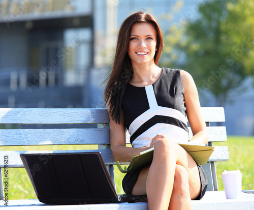 Young business woman using laptop outdoors