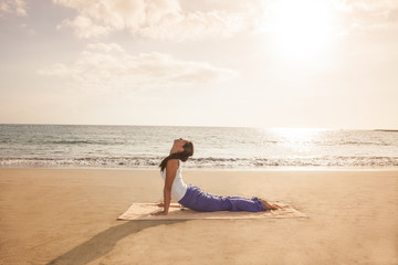 Young woman practicing yoga cobra pose on the beach near the oce