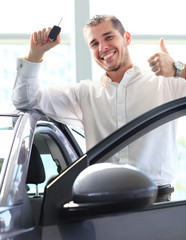 young man with the keys of his new car and Thumbs Up