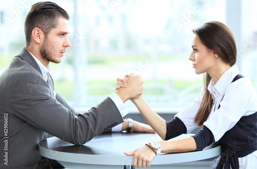 businesswoman and businessman arm wrestling during meeting