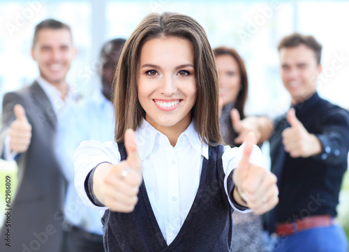 attractive businesswoman with team in office showing thumbs up