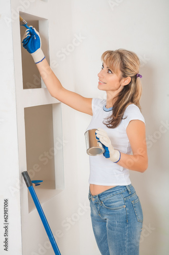 beautiful female painter painting wall