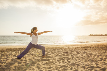 Young woman practicing yoga warrior pose on the beach at sunset