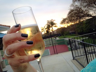 Woman's hand holding champagne glass outdoors during celebration