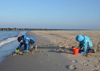 Kinder spielen am Strand im Winter