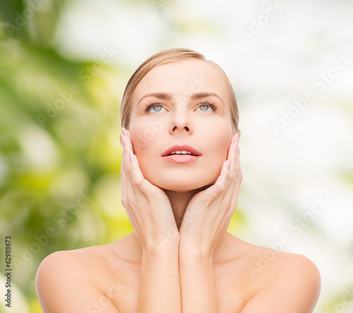 beautiful woman touching her face and looking up
