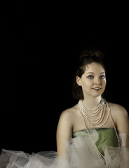 Pretty young woman wearing green tulle and pearls