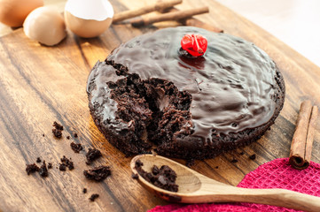 Round homemade chocolate cake on wooden cutting board